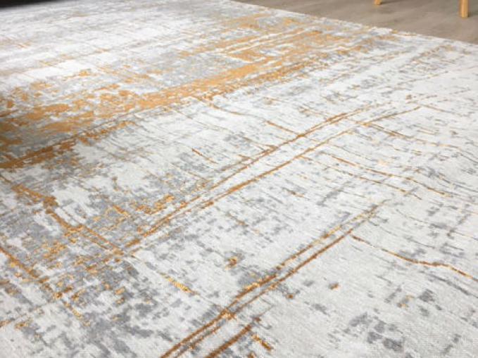 mechanisch dun tapijt in grijs en goud